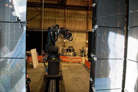 """Fig. 9: Hovedparten af scenerne uden for rumkabinerne blev optaget i """"Sandy's Cage"""", hvor Bullock og Clooney var anbragt i diverse ophæng og omgivet af LED-lyspaneler, hvorpå CG-elementerne afvikledes og dermed afgav """"naturalistisk"""" lys på spillerne. Under de hæsblæsende scener blev Bullock fastgjort til et bevægeligt rig, hendes bevægelse synkroniseret til CG-baggrundene, alt imens det robotstyrede kamera kørte sine helt egne baner. Som Bullock gør opmærksom på, var hun prisgivet, hvis et robotstyret kamera ramlede ind i hende (""""Behind the Scenes Featurette"""" 2013)."""