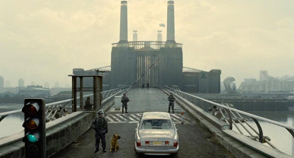 """Fig. 1: Establishing shot: indstillingen der introducerer """"The Court of the Crimson King""""-scenen i Children of Men er en tydelig henvisning til Pink Floyds album Animals (1977). Både film og album har en lyserød gris svævende mellem skorstenene på den ikonografiske Battersea Power Station i London."""