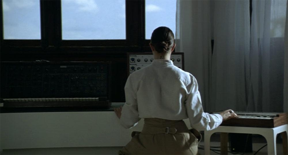 Fig. 6: Et af gruppens medlemmer (Asia Argento) spiller på synthesizer for nogle mennesker, der ligger udenfor i haven.