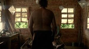 """Fig. 6: Errols enorme ryg tårner sig op i forgrunden mens faderen, der ligger bundet, anes foran ham. Det ulækre understreges af Errols replik: """"Them flies are getting thick…"""""""
