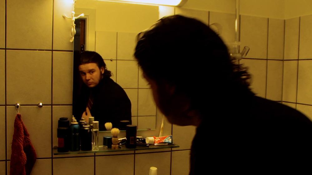 Fig. 5: Henrik betragter sig selv i spejlet, måske som et lille vink om, at han i filmen bliver tvunget til at se indad og tage sit liv op til revision.
