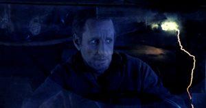Fig. 8. Via en dobbelteksponering af Jackies maniske sammenbrud bag rattet og det lynende dødemandslandskab illustreres, at han er ankommet til dødsriget.