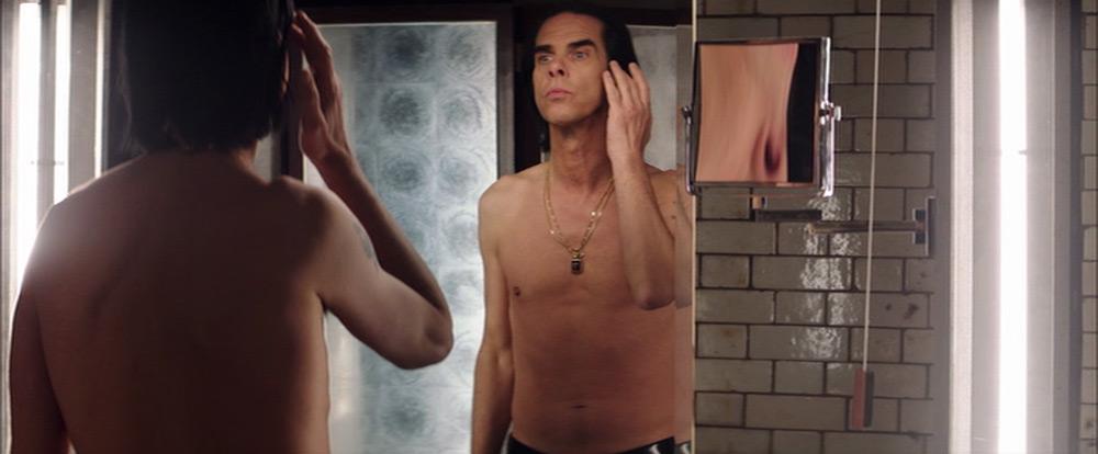 Fig. 3. I en steril konstruktion af lys og spejle studerer Nick Cave sig selv pertentligt, som om figuren i spejlet er en anden.
