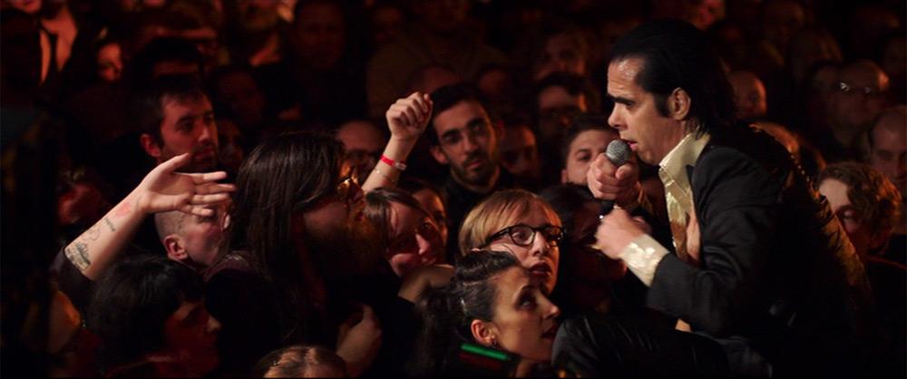 """Fig. 9. Nick Cave fører i en smuk samhørighed hånden fra en kvindelig fan op til sit hjerte, mens han i musikken spørger """"Can you feel my heartbeat?"""""""