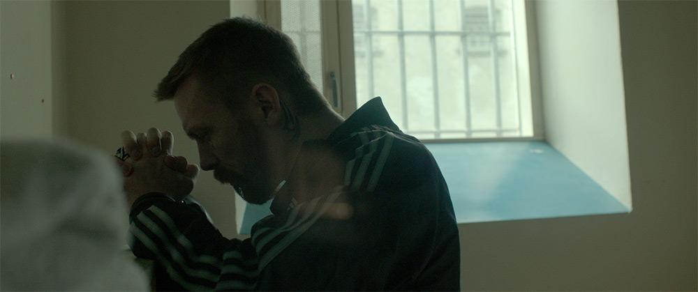 Fig. 10: Lars beder en bøn, inden han forlader fængslet. Det rigtige fængsel venter tilbage i rockerklubben.