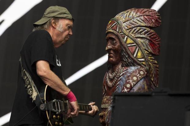 Fig. 2: Young spiller tråd for træindianeren på sin seneste Earth-tour. Figuren er en rekvisit tilbage fra indspilningerne af musicalen Human Highway i 1982.