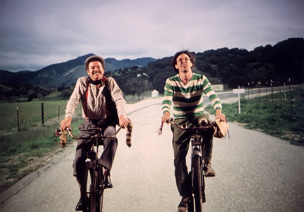 Fig. 7: Hovedfortællingen i Human Highway om livet på dineren og benzintanken nær det lokale atomkraftværk er ren Morten Korch. Her er det Neil Young som tankpasseren Lionel Switch og hans kollega Fred Kelly (spillet af Russ Tamblyn a.k.a. Dr. Lawrence Jacobi fra Twin Peaks og bandelederen Riff fra West Side Story) cyklende på vej til arbejde.