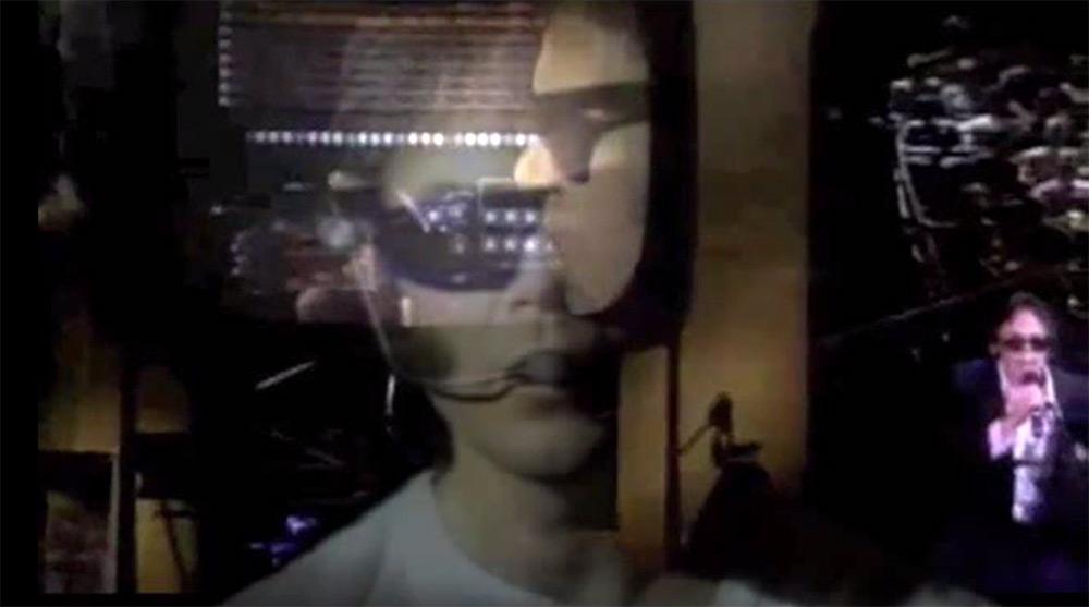 """Fig. 12: """"Mr. Soul"""" bliver fortolket med robotstemme og hypermedieret billedside, hvor Youngs performance live og på scenens gigantiske tv-skærm overlapper hinanden i en dobbelteksponering."""
