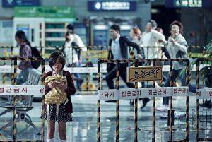 Fig. 7: Den unge datter Soo-an i en indstilling, der viser hendes isolation og fremmedgjorthed overfor det kaos der omgiver hende. Den unge pige, som spilles til empatisk perfektion af Kim Soo-an, bliver et meget symbolsk billede for det der er værd at kæmpe for i en verden, hvor egoisme og voldelige handlinger overskygger det menneskelige nærvær.